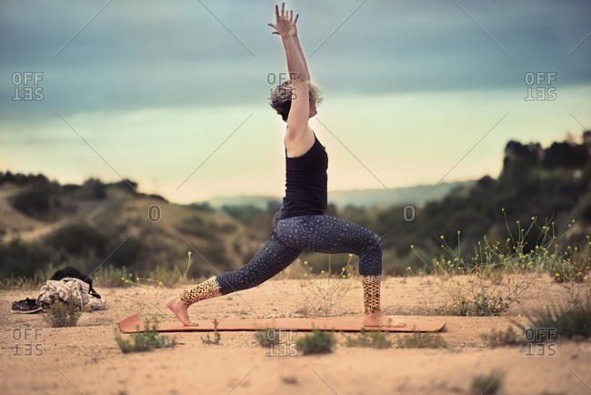 Woman doing the warrior one yoga pose outdoors