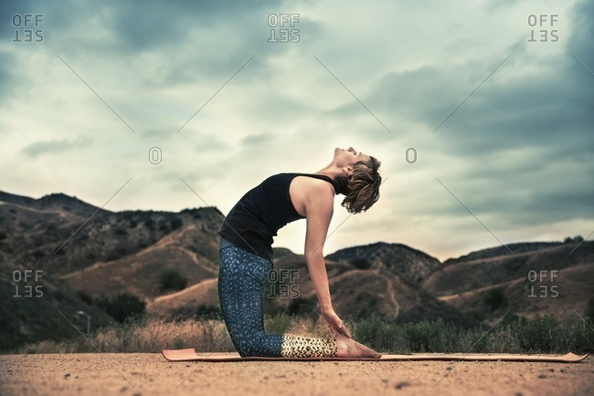 Woman practicing her camel yoga pose outdoors
