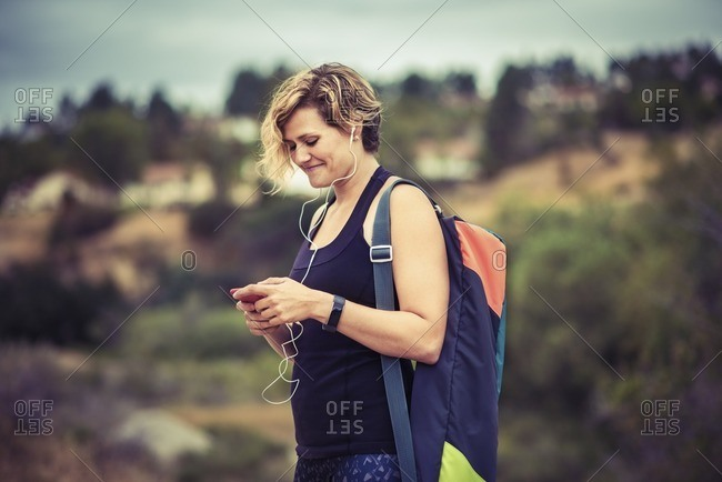 Happy woman standing outside listening to music on her phone