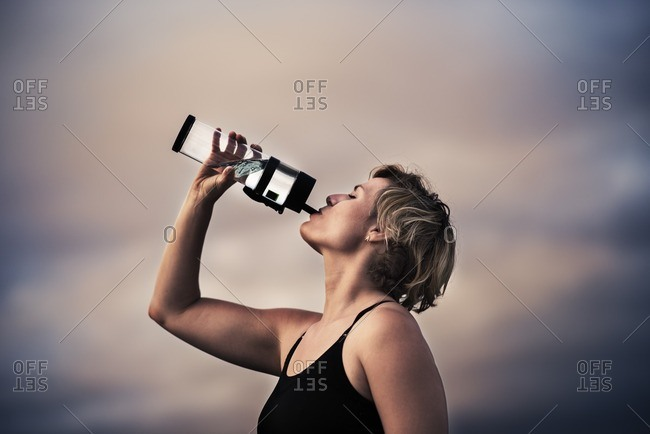 Woman replenishing with water during a workout