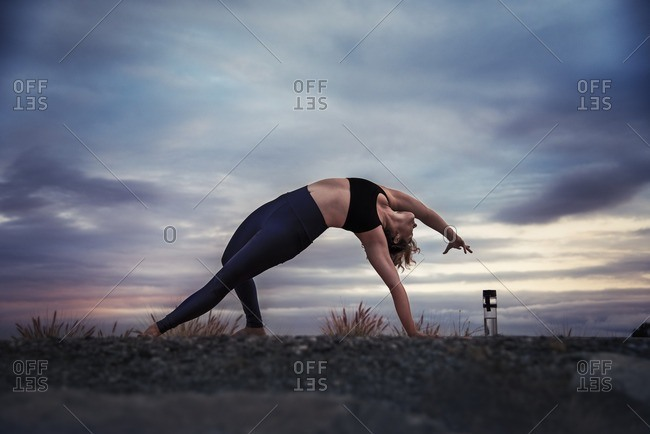 Woman practicing wild thing yoga pose outdoors