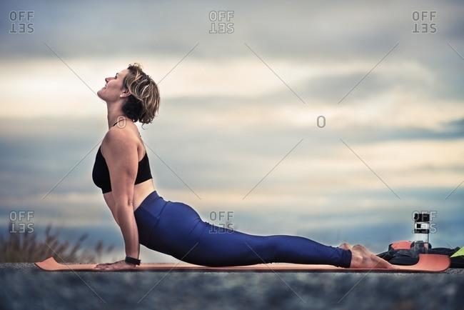 Woman practicing a cobra yoga pose outdoors