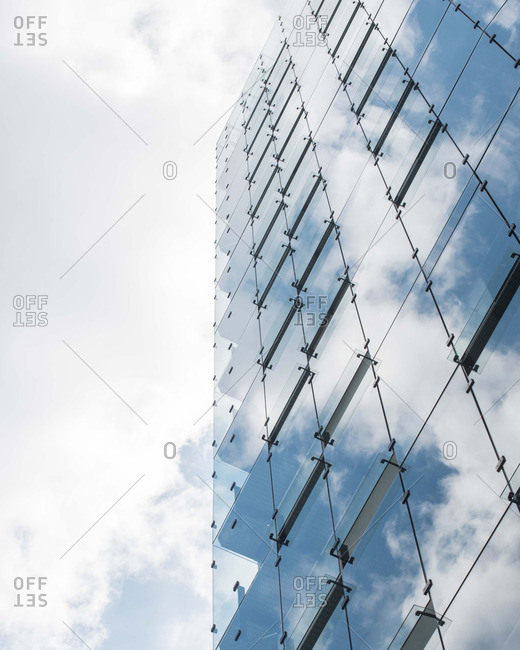 Building with glass panels reflecting cloudy sky