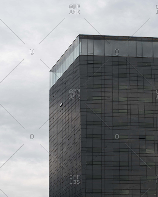 Opaque glass modern building with transparent row of glass at top
