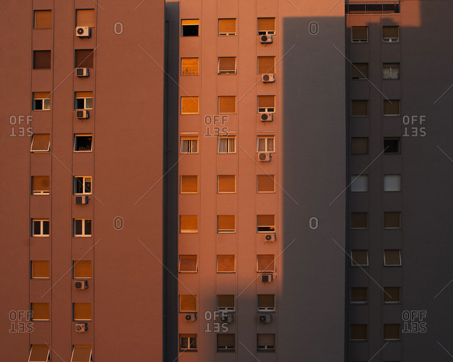 Sunset light and shadow on apartment building with rows of square windows
