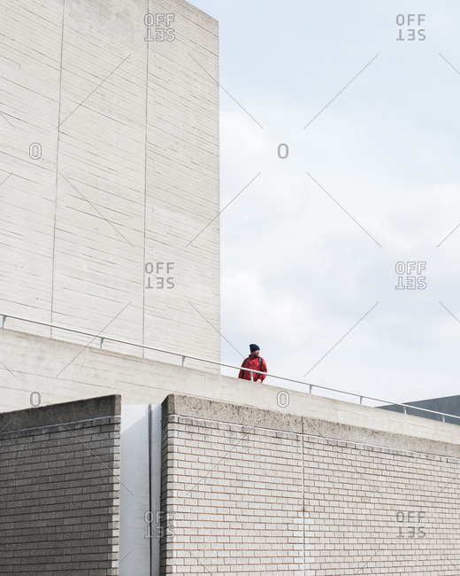 4/1/16: Man in red jacket overlooking street from walkway of minimalist building