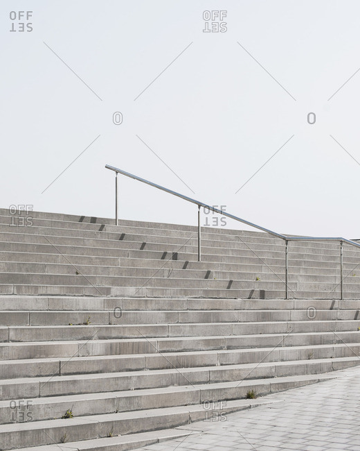 Set of cement stairs with railing in middle