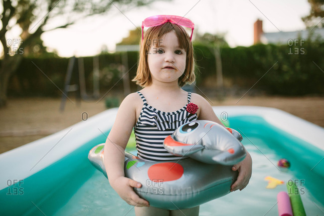Toddler girl standing in pool with float