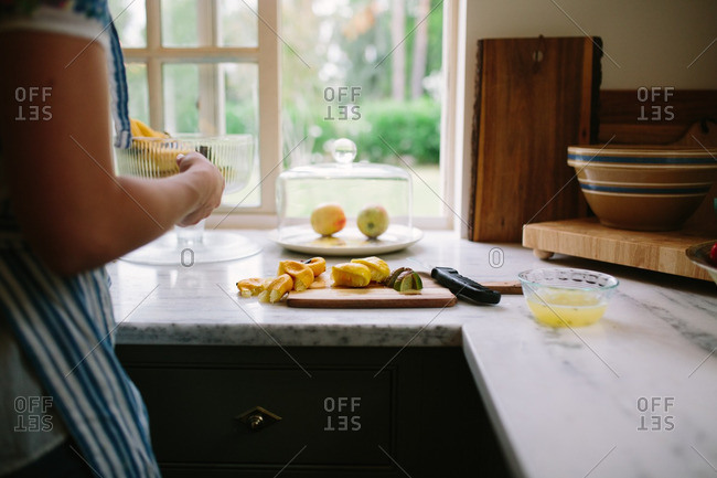 Person making fresh squeezed citrus juice at kitchen counter