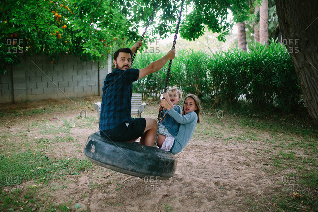 Man and two children swing on backyard tire swing
