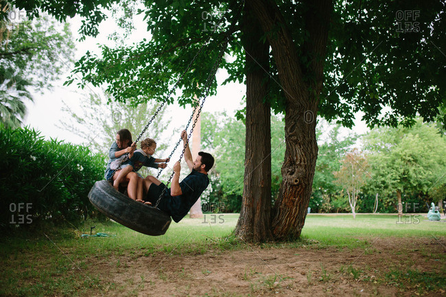 Father with two children riding on tire swing