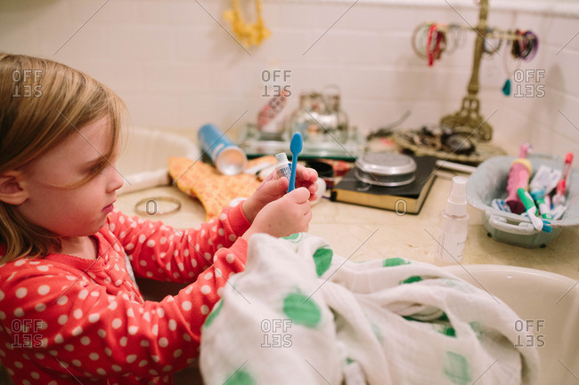 Young girl at bathroom counter with toothbrush and toothpaste
