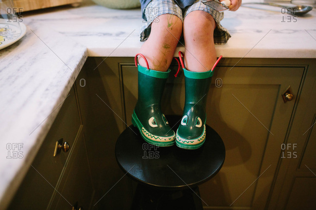 Toddler in green alligator boots with drawings on his legs sits on kitchen counter