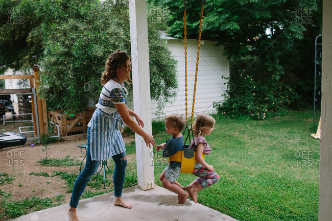 Two young children sit back-to-back in swing while mother pushes them