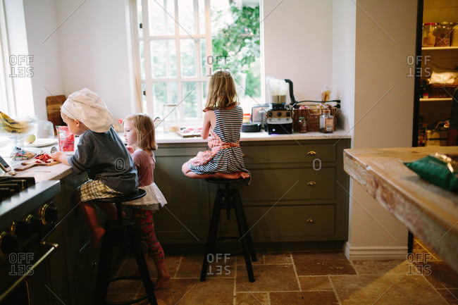 Three young children working at kitchen counter