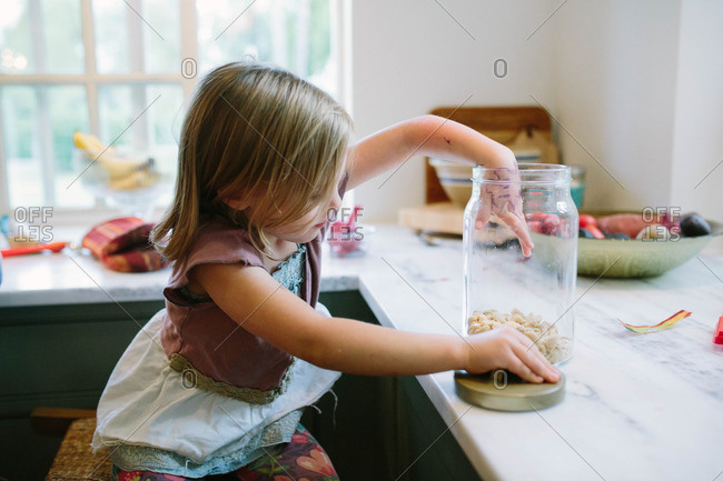 Young girl reaching in glass jar of nuts