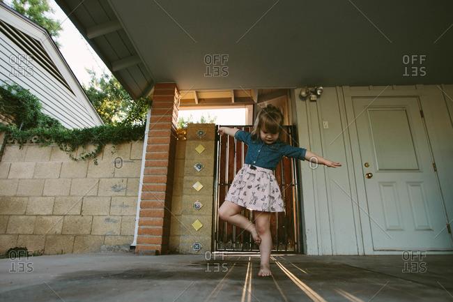 Young girl playing on shadows on sidewalk