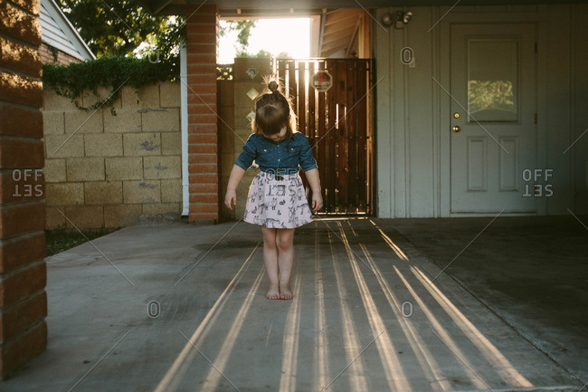 Toddler girl playing on sidewalk with stripes of sunlight
