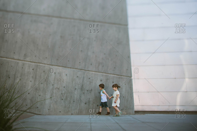 Boy and girl holding hands outside modern cement building