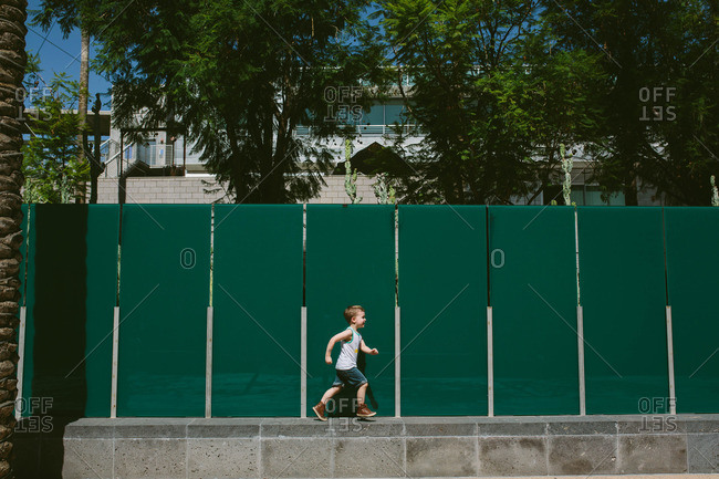 Boy running on wall against green fence