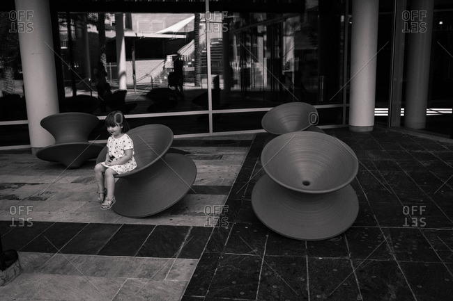 Young girl sitting in round modern chairs outside building