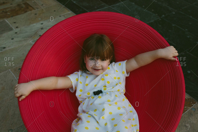 Portrait of young girl sitting in a round red chair