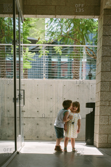 Boy kisses his toddler sister outside building