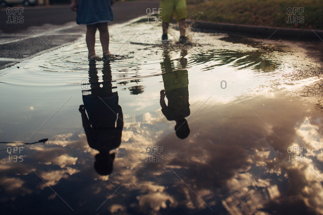 Reflection of two toddlers in puddle at sunset