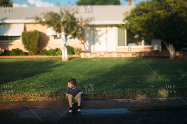 Toddler boy sitting on curb in front of home