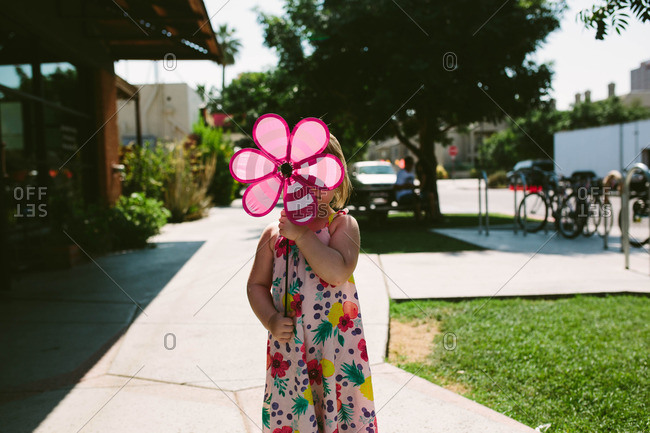 Toddler girl with flower pinwheel on sidewalk