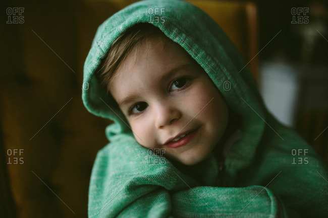 Close-up of toddler boy in green hoodie