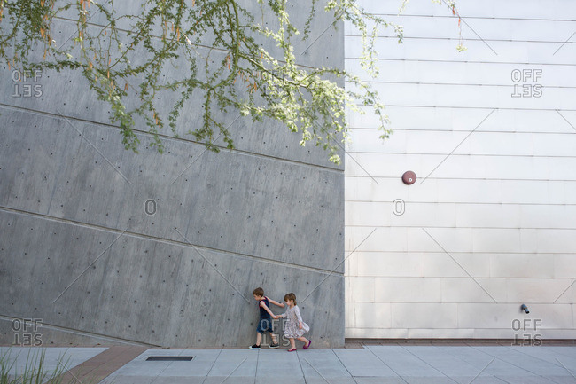 Toddler boy and girl explore the grounds of modern public building