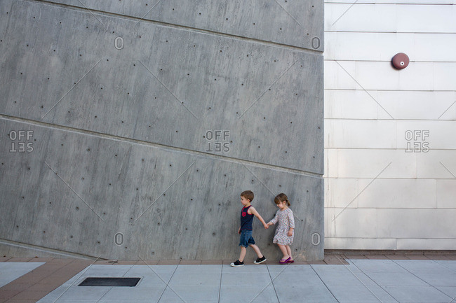 Boy holds sister's hand as they walk outside modern concrete building