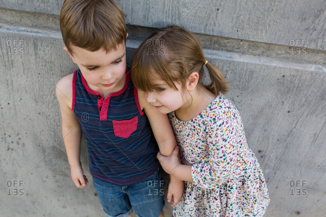 Toddler girl holds onto her brother's arm against cement wall