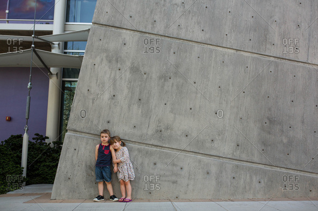 Toddler boy and girl stand against wall outside museum
