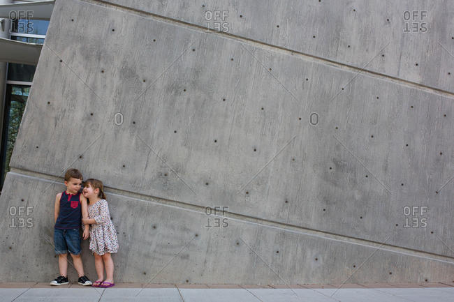Happy toddler siblings standing against wall outside museum