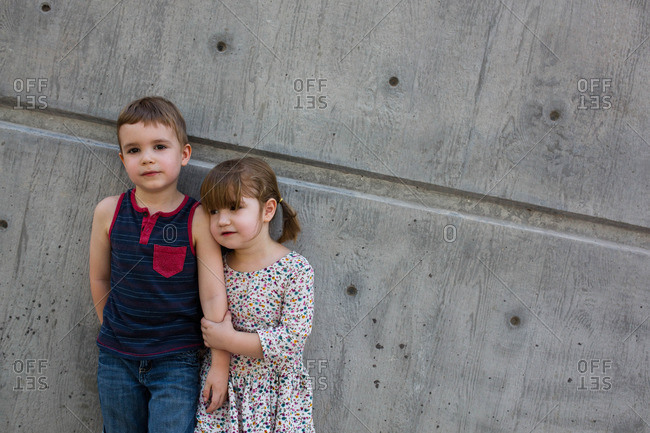 Young brother and sister stand together against cement wall