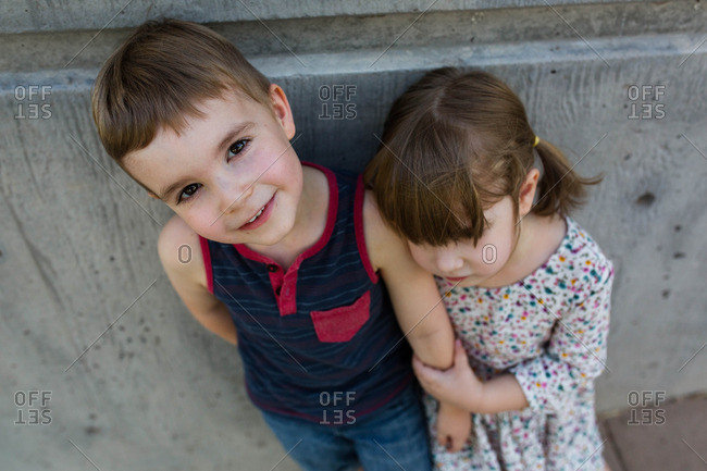 Elevated view of young boy standing against cement wall with sister