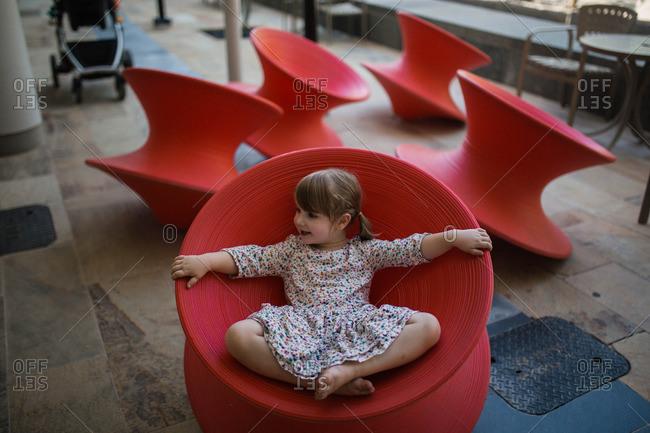 Toddler girl sitting in red Spun Chair