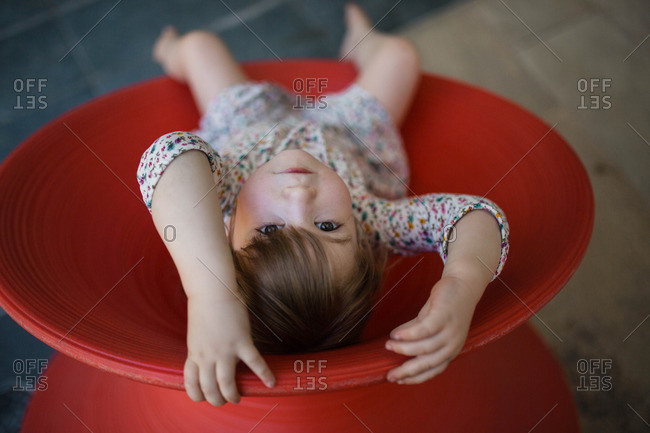Toddler girl playing in red Spun Chair