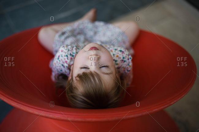 Toddler girl relaxing in modern red Spun Chair