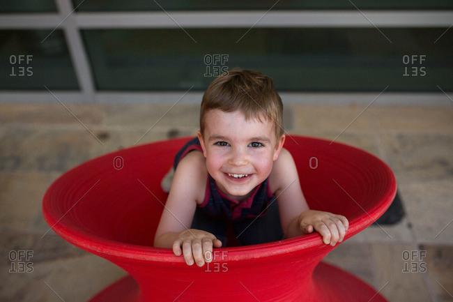 Toddler boy peeking out of modern red Spun Chair
