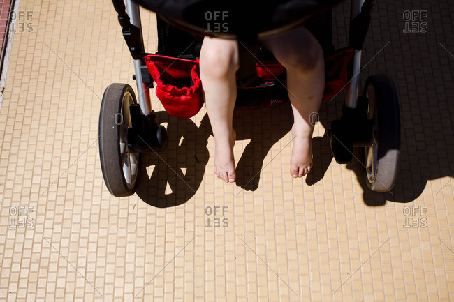 Baby's bare feet dangling off stroller