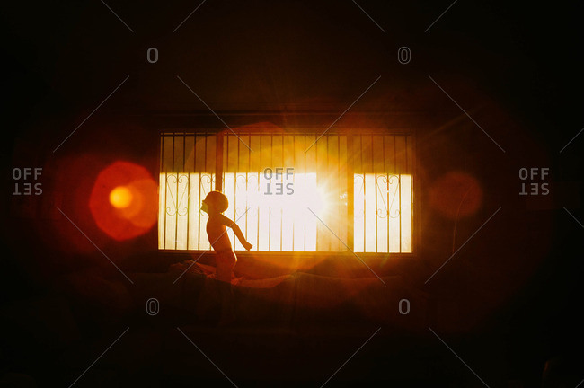 Child silhouetted on couch while playing in living room