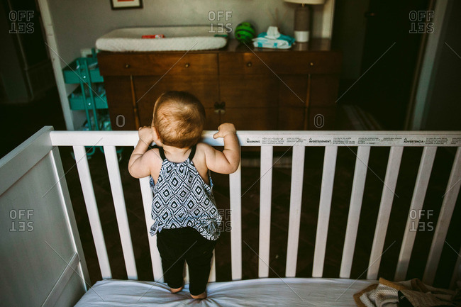 Baby girl peeking over edge of crib in bedroom