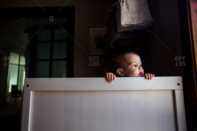 Infant peeking over edge of crib