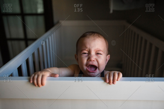 Baby crying while holding onto edge of crib