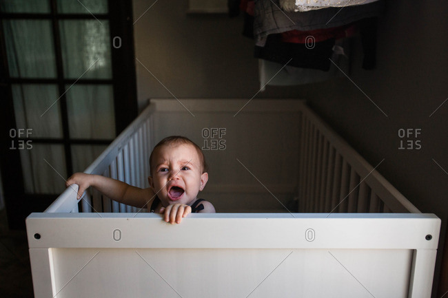 Crying baby standing up in crib