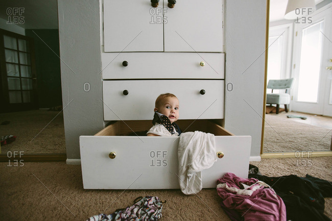 Baby playing in chest of drawers