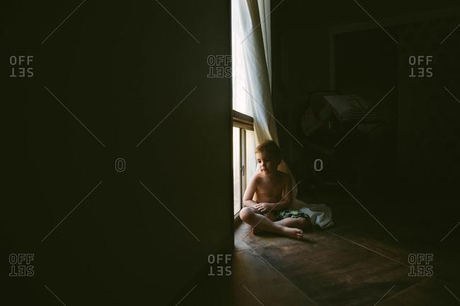 Boy sitting on floor behind curtain